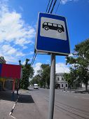 stock photo of distortion  - Road sign with a picture of a bus stop on a city street with wide angle distortion view - JPG