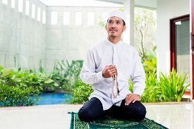 picture of muslim man  - Asian Muslim man praying at home sitting on prayer carpet in his house in front of the tropical garden - JPG