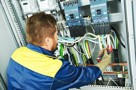 picture of electrical engineering  - adult electrician builder engineer making electrical measure with equipment in fuseboard - JPG