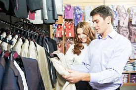 picture of apparel  - Young man and woman choosing suit jacket during apparel shopping at clothing store - JPG