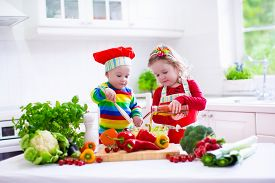 stock photo of twin baby  - Kids cooking fresh vegetable salad in a white kitchen - JPG