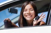 Happy Asian girl teen driver showing new car keys. Young woman smiling driving new car holding key.  poster