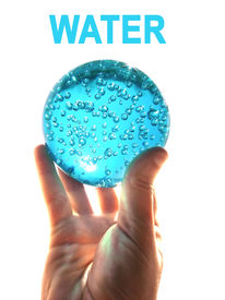 stock photo of water pollution  - A hand holding a glass ball  - JPG