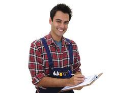 stock photo of blue-collar-worker  - happy serviceman or craftsmen taking notes - JPG