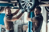 Two Mechanics Looking At Camera While Wheel Check. Caucasian Men Checking Wheel Bearings In Car Work poster