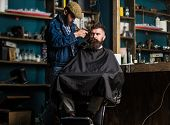 Barber With Clipper Trimming Hair On Temple Of Bearded Client. Hipster Client Getting Haircut. Barbe poster