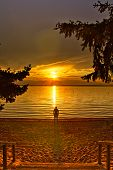 Stairs Leading Down To A Beach With A Man Watching The Sun Setting Over Waskesiu Lake In Prince Albe poster