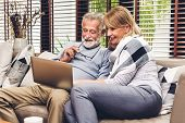 Senior Couple Relaxing And Using Laptop Computer Together Sitting On Sofa In Living Room At Home.ret poster
