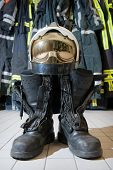 stock photo of firehose  - A helmet and bootz on the floor in a firestation ready to be used by firefighters - JPG