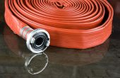 picture of firehose  - A rolled up firehose on the wet floor in a firestation used by firefighters - JPG