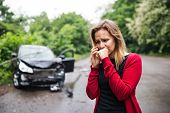 A Young Woman With Smartphone By The Damaged Car After A Car Accident, Making A Phone Call. poster