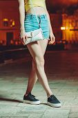 Girl In Short Shorts With Clatch Posing In Night City poster
