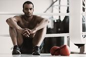 Portrait Of Black Male Boxer Sitting On Ring. Portrait Of Muscular African Man In Sportswear Sitting poster
