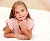 Adorable Smiling Little Girl Child Is Resting On A Bed At Home poster