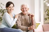 Happy Senior Man With Walking Stick And Smiling Granddaughter poster