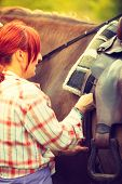 Taking Care Of Animals, Horsemanship, Equine Concept. Redhead Cowgirl Getting Horse Ready For Ride O poster