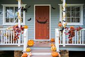 Halloween pumpkins and decorations outside a house poster