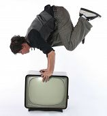 image of tv sets  - Man hold balance on retro TV set - JPG
