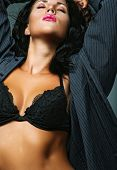Tanned beautiful torso of athletic woman in black lingerie and stockings