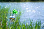 stock photo of sounding-rod  - Fishing bite alarm bell in readinesson blurred green vegetation and river - JPG