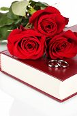 Wedding rings with roses on bible isolated on white