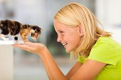 stock photo of pre-adolescent girl  - loving teen girl playing with pet kitten at home - JPG