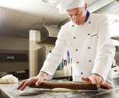 stock photo of pastry chef  - Chef preparing pastry in his kitchen - JPG