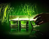 picture of absinthe  - Hand holding one of three glasses of green absinth with fume going out - JPG