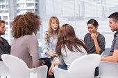 stock photo of helping others  - Woman crying during therapy session with other people and therapist - JPG