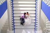 Beautiful young bride and groom sitting on the stairs