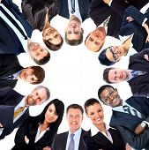 stock photo of huddle  - Group of business people standing in huddle - JPG