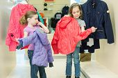 Two girls try on clothes in a store childrens clothes