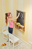 Little girl draws with chalk on blackboard