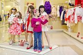 Little girl performs fashion doll, standing together with group of dressed mannequins