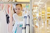 Little girl looks over dresses hanging on stand in clothing store