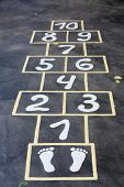 stock photo of hopscotch  - Hopscotch painted indelible ink on black asphalt for children outdoor - JPG