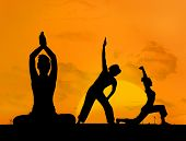 Silhouette of women doing yoga in front of the sunset