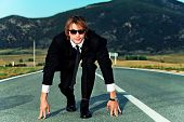 Businessman is at the start of running on the highway. Business struggle concept.