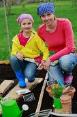 Gardening - sowing seeds to the soil, girl helping mother in the garden