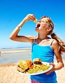 stock photo of high calorie foods  - Child eating fast food at beach outdoor - JPG