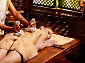 picture of panchakarma  - Woman having Ayurveda massage with herbal ball - JPG