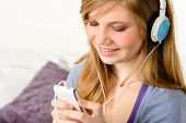Fresh adolescent girl listening to music with mp3 player