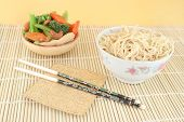 picture of lo mein  - delicious chinese lo mein noodles and stir fry vegetables with cashews on a bamboo place mat with chopsticks - JPG