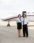 Full length portrait of confident airhostess and pilot standing together against private jet