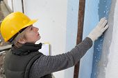 picture of insulator  - Construction inspector examine styrofoam insulation of house facade wall - JPG