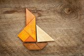 stock photo of wood pieces  - abstract picture of a sailing yacht built from seven tangram wooden pieces over a rustic  barn wood - JPG