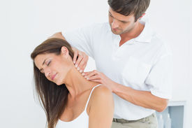 picture of chiropractor  - Male chiropractor massaging a young woman - JPG