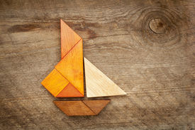 picture of tangram  - abstract picture of a sailing yacht built from seven tangram wooden pieces over a rustic  barn wood - JPG