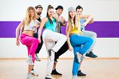 stock photo of dancing  - Young men and women dancing modern group choreography in dance school - JPG