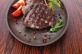 stock photo of peppercorns  - fresh roast beef fillet mignon on old retro style cast iron pan on retro wooden table as background with rosemary peppercorn and tomatoes - JPG